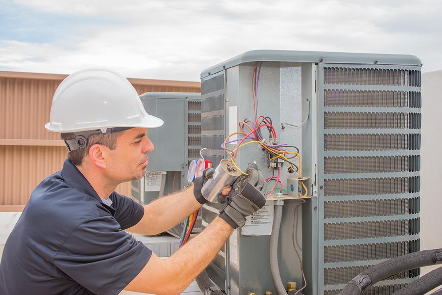 Hvac Tech checking a run capacitor on a condenser